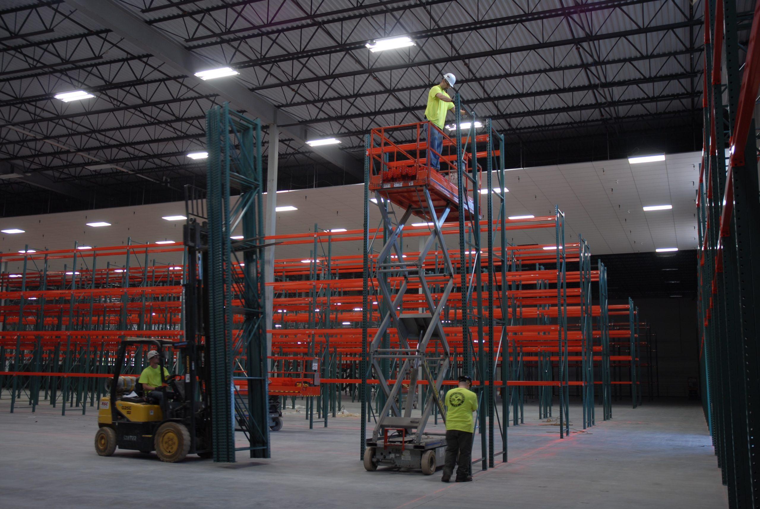 pracovníci provádí montáž průmyslových regálů za pomoci výsuvné plošiny