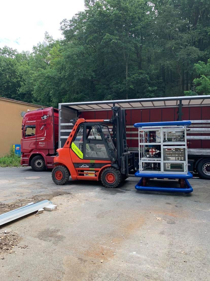vysokozvižný vozík stěhuje stroj a nakládá ho do kamionu